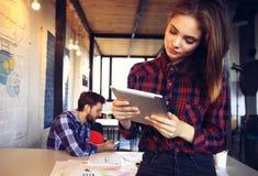Усмехаясь молодые женщины используя цифровую таблетку Стоковые Фото