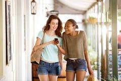 Усмехаясь молодые женщины идя совместно используя мобильный телефон Стоковое Фото