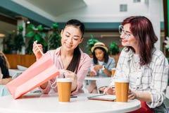 Усмехаясь молодые женщины сидя на таблице и смотря в хозяйственной сумке Стоковое Изображение