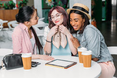 Усмехаясь молодые женщины сидя на таблице с бумажными стаканчиками и держать новые стильные ботинки Стоковая Фотография