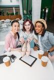 Усмехаясь молодые женщины сидя на таблице с бумажными стаканчиками и показывать новые стильные ботинки Стоковые Изображения