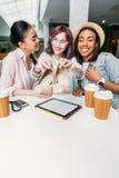 Усмехаясь молодые женщины сидя на таблице с бумажными стаканчиками и показывать новые стильные ботинки Стоковые Изображения RF