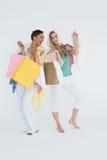 Усмехаясь молодые женщины стоя с хозяйственными сумками Стоковое Изображение