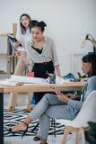 Усмехаясь молодые дизайнеры работая с светокопией и цифровой таблеткой в современном офисе Стоковые Фото