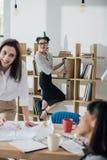 Усмехаясь молодые коммерсантки работая совместно в современном офисе Стоковые Фотографии RF