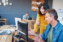 Усмехаясь молодые коллеги офиса говоря совместно над компьютером Стоковая Фотография