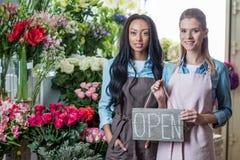 Усмехаясь молодые многонациональные флористы держа открытый знак и усмехаясь на камере в цветочном магазине Стоковые Фото