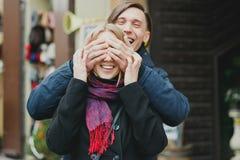 Усмехаясь молодые пары внешние Человек покрывает его глаза подруги делая сюрприз Стоковое фото RF