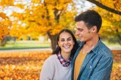 Усмехаясь молодые пары outdoors в парке в осени Стоковая Фотография