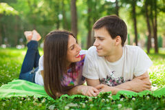 Усмехаясь молодые любовники вне в лежать парка Стоковые Изображения RF