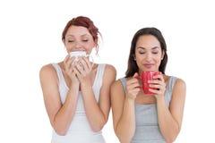 2 усмехаясь молодых женских друз выпивая кофе Стоковая Фотография RF