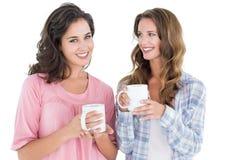 2 усмехаясь молодых женских друз выпивая кофе Стоковое фото RF