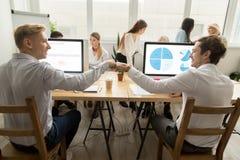 Усмехаясь мужской кулак сотрудников bumping на рабочем месте в coworking  Стоковая Фотография