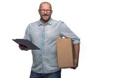 Усмехаясь мужской курьер поставляя пакет стоковые изображения