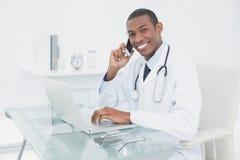 Усмехаясь мужской доктор используя мобильный телефон и компьтер-книжку Стоковое фото RF