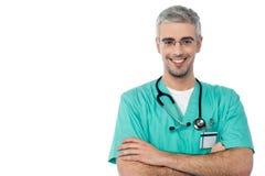Усмехаясь мужской доктор при пересеченные оружия стоковое изображение