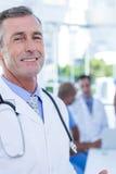 Усмехаясь мужской доктор смотря камеру пока его коллеги работают Стоковые Изображения