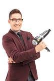 Усмехаясь мужской парикмахер держа сушильщика дуновения стоковая фотография