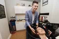 Усмехаясь мужской парикмахер моя волосы женского клиента в салоне стоковое фото rf