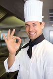 Усмехаясь мужской показывать кашевара одобренный подписывает внутри кухню Стоковые Изображения