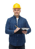 Усмехаясь мужской построитель в шлеме с доской сзажимом для бумаги Стоковое Изображение RF