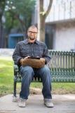 Усмехаясь мужской студент университета сидя на стенде Стоковое фото RF