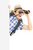 Усмехаясь мужской турист loooking через бинокулярное за панелью Стоковая Фотография RF