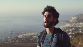 Усмехаясь мужской hiker смотря прочь пока dinking вода против неба сток-видео