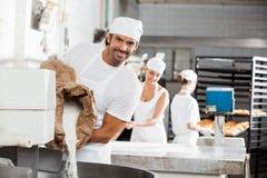 Усмехаясь мука мужского хлебопека лить в замешивая машине Стоковые Изображения