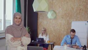 Усмехаясь мусульманская женщина в офисе сток-видео