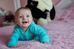 Усмехаясь младенец лежа в кровати pearent Стоковые Фотографии RF
