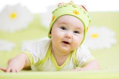 Усмехаясь младенец лежа на зеленом цвете Стоковые Изображения