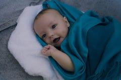 Усмехаясь младенец предусматриванный в голубом одеяле Стоковое фото RF