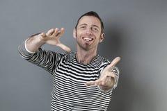 Усмехаясь напористый человек 40s хватая что-то Стоковое фото RF