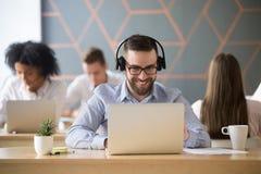 Усмехаясь наушники бизнесмена нося наблюдая видео или советуют с Стоковое Фото