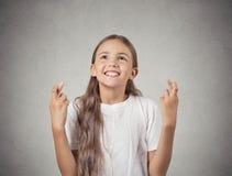 Усмехаясь надеющийся девушка пересекая ее надеяться пальцев стоковые изображения rf