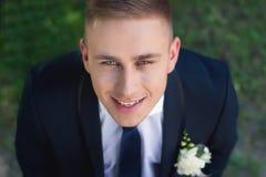 Усмехаясь невеста смотрит в камеру поднимая его голову Стоковое фото RF