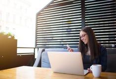 Усмехаясь новости чтения студента женщины в сети через мобильный телефон, усаживание в кофейне с тетрадью Стоковые Фото
