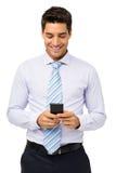 Усмехаясь обмен текстовыми сообщениями бизнесмена на умном телефоне стоковое фото