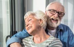Усмехаясь обнимать старика и женщины стоковые изображения
