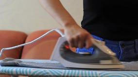 Усмехаясь одежды женщины утюжа используя утюг на утюжа доске после прачечной дома акции видеоматериалы