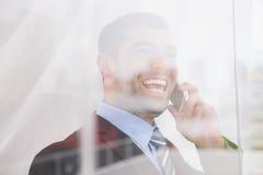 Усмехаясь окно бизнесмена вне на камере на телефоне Стоковая Фотография RF