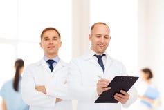 Усмехаясь доктора в белых пальто с доской сзажимом для бумаги Стоковое Изображение RF