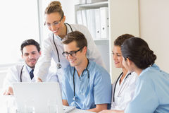 Усмехаясь доктора и медсестры обсуждая над компьтер-книжкой Стоковые Фотографии RF