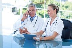 Усмехаясь доктора работая совместно на таблетке Стоковое Фото