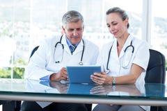 Усмехаясь доктора работая совместно на таблетке Стоковое Изображение