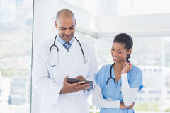 Усмехаясь доктора работая с таблеткой совместно Стоковые Фотографии RF