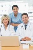 Усмехаясь доктора с компьтер-книжкой на медицинском офисе Стоковая Фотография RF