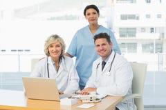 Усмехаясь доктора с компьтер-книжкой на медицинском офисе Стоковое Изображение RF