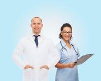 Усмехаясь доктора с доской сзажимом для бумаги и стетоскопами Стоковые Изображения